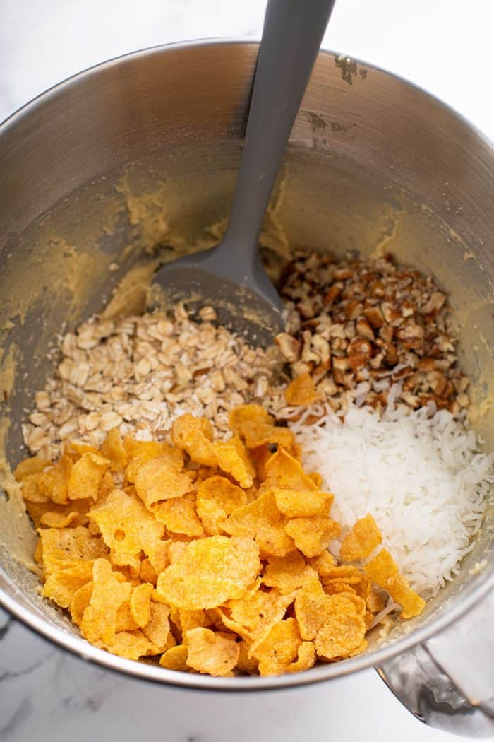 Spatula stirring oats, pecans, coconut, and cornflakes into cookie dough in a metal mixing bowl