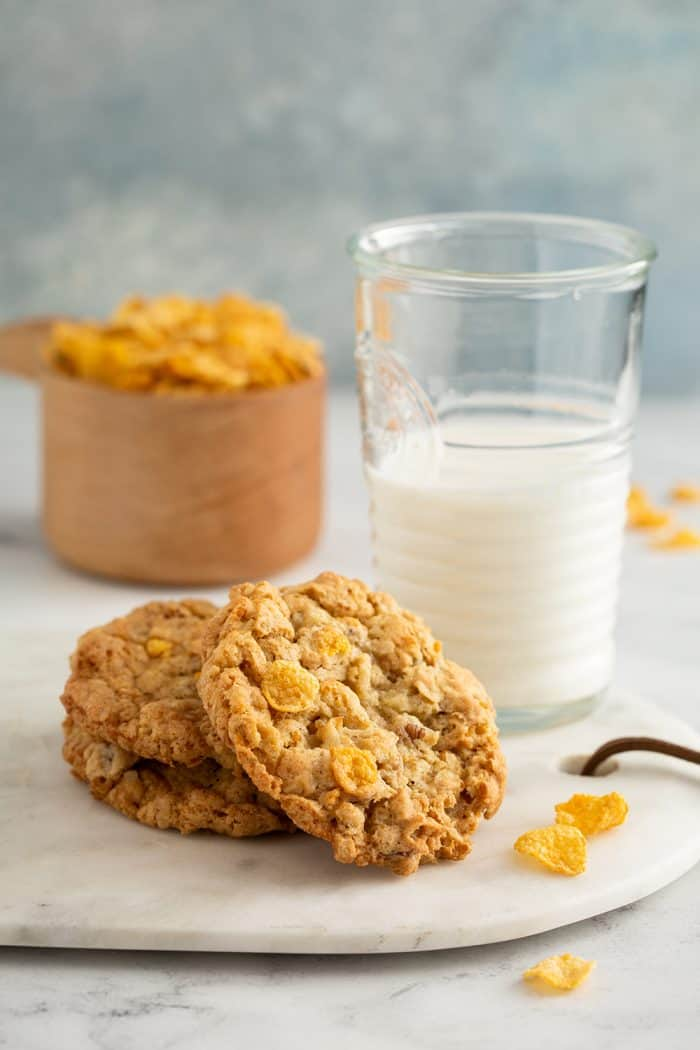 Three cornflake cookies next to a glass of milk with a measuring cup of cornflakes in the background