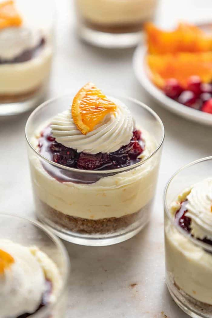 Mini cranberry cheesecake in glass dishes topped with whipped cream and a slice of orange