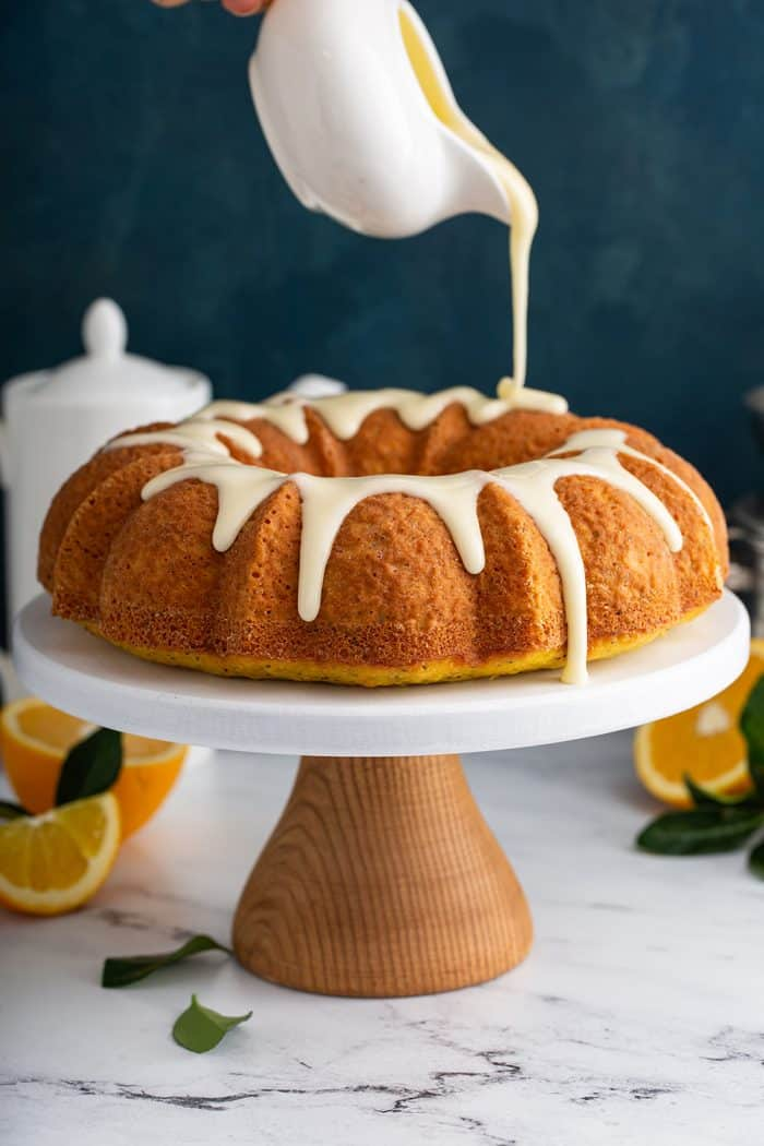 Glaze being poured over a citrus poppy seed cake on a white cake stand