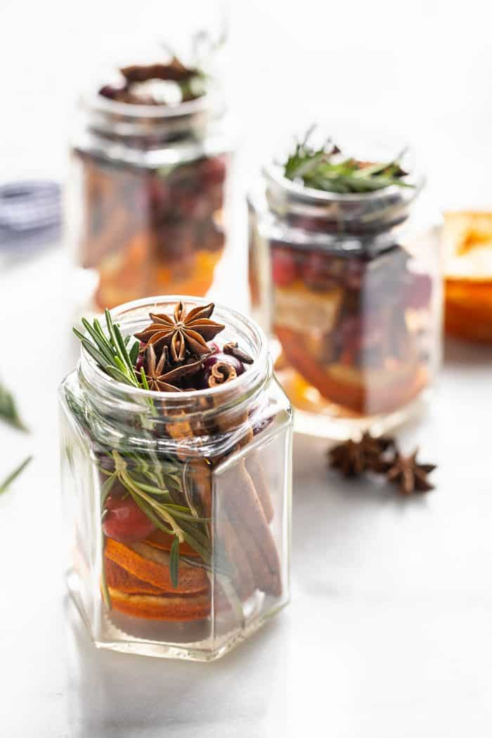 Three open glass jars filled with stovetop potpourri