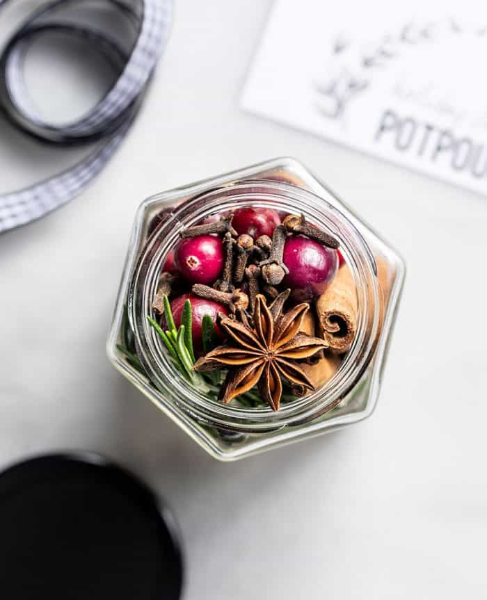Overhead view of an open jar filled with stovetop potpourri on a marble counter