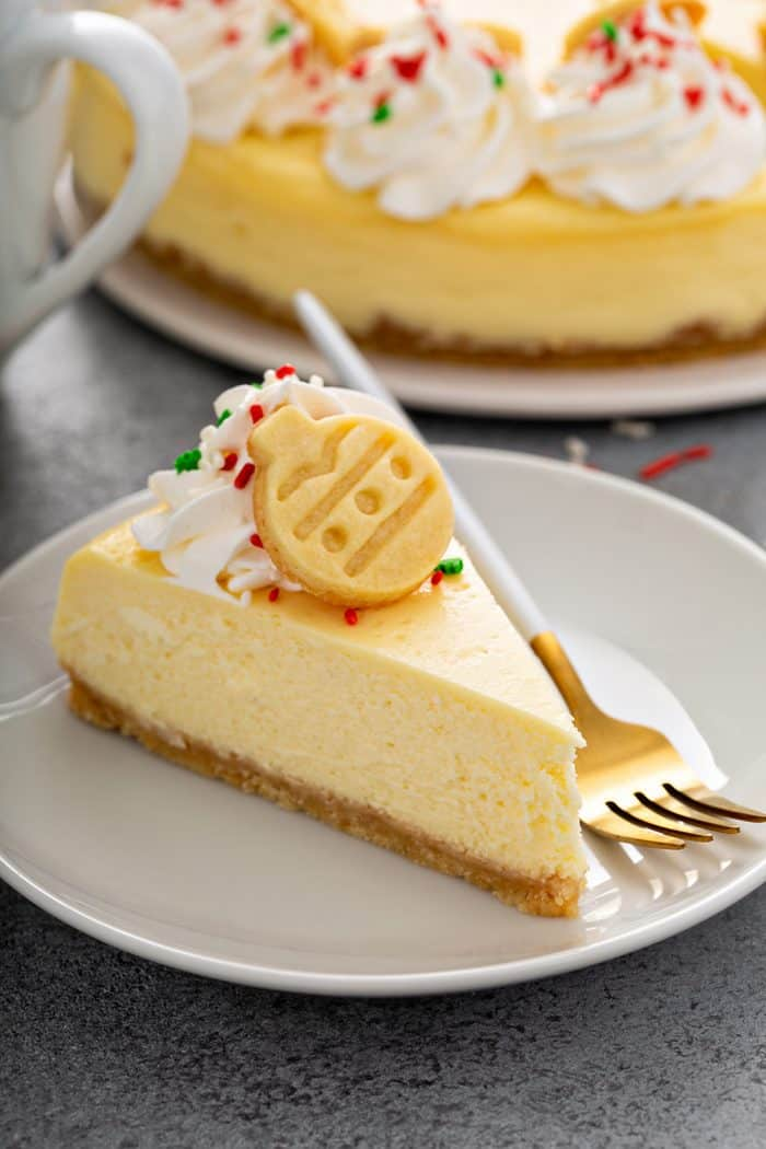 Slice of sugar cookie cheesecake next to a fork on a white plate