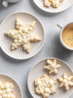 Assorted snowflake sugar cookies on white plates next to cups of coffee