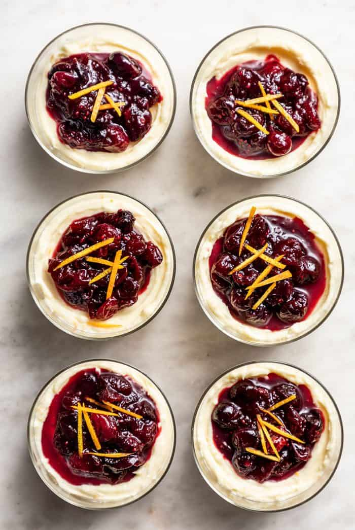 Six no-bake cranberry cheesecakes in glass dishes lined up on a marble counter
