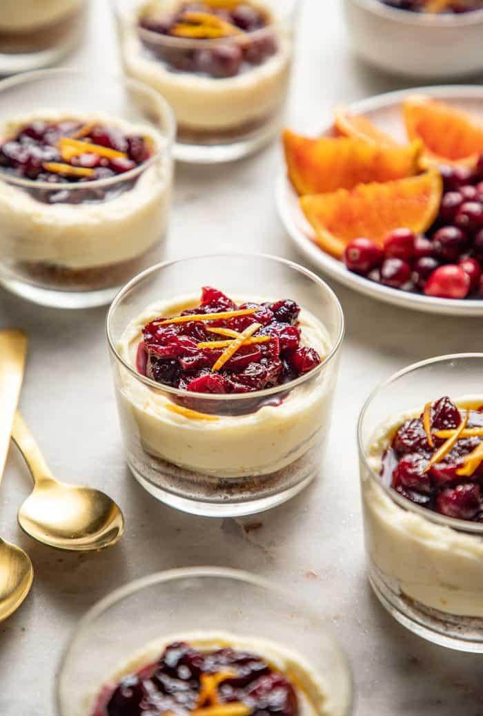 Cranberry cheesecakes topped with cranberry sauce and orange zest on a marble counter