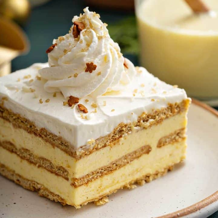 Slice of eggnog eclair cake topped with whipped cream and sparkling sugar on a white plate