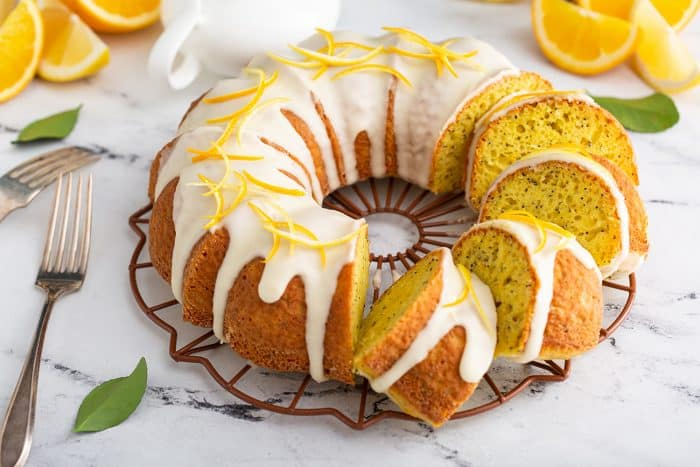 Sliced citrus poppy seed cake on a marble counter
