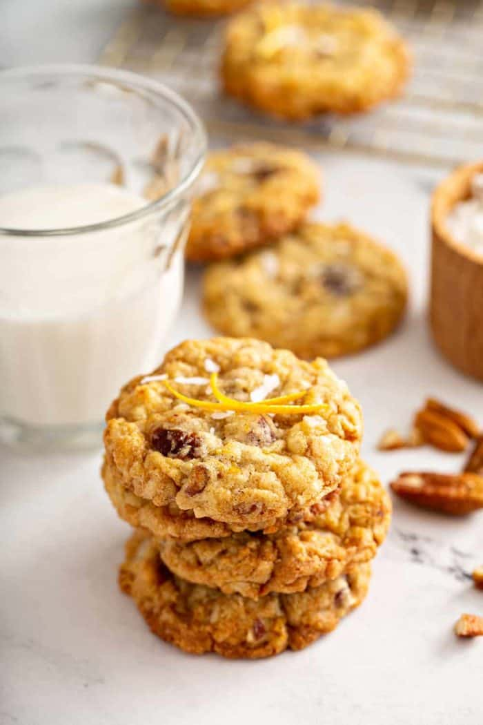 Stack of 4 ambrosia cookies on a marble counter with a glass of milk in the background