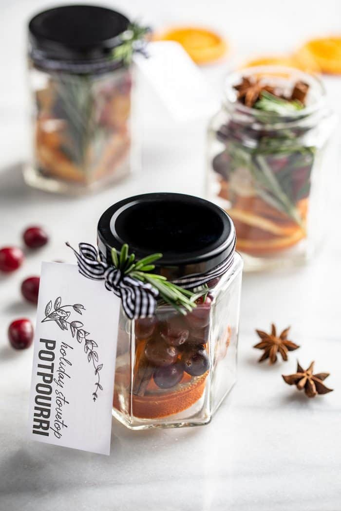Stovetop potpourri in 3 glass jars tied with gift tags on a marble counter