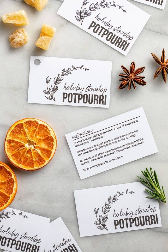 Printable holiday stovetop potpourri gift tags laid out on a counter with dried oranges and spices