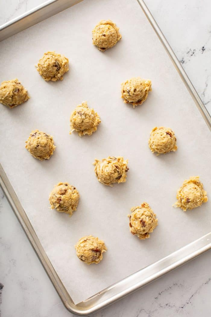 Unbaked ambrosia cookies on a parchment-lined baking sheet