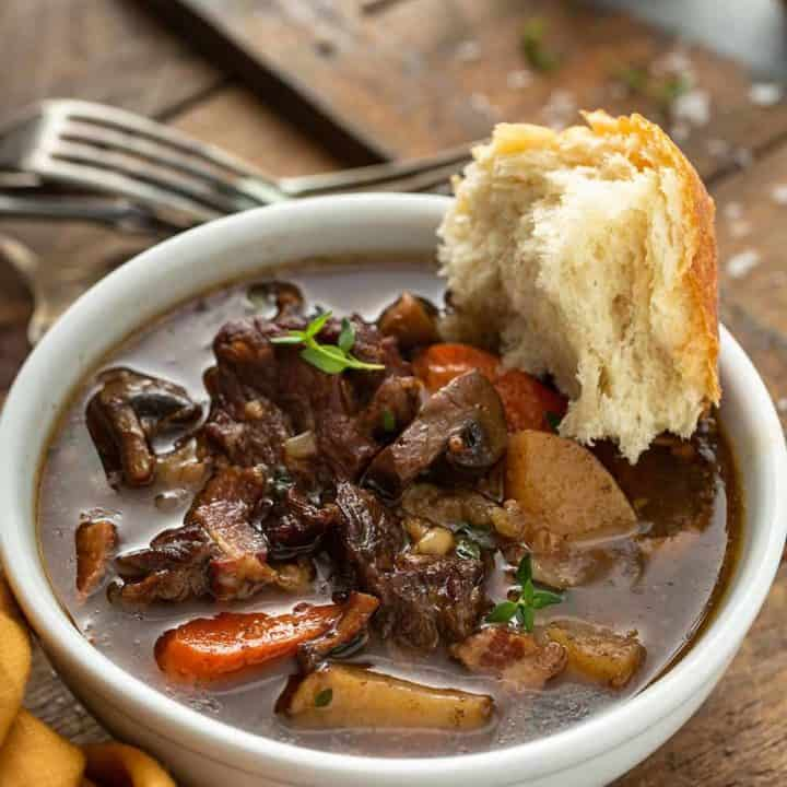 Crusty bread dipped into a bowl of beef and barley stew