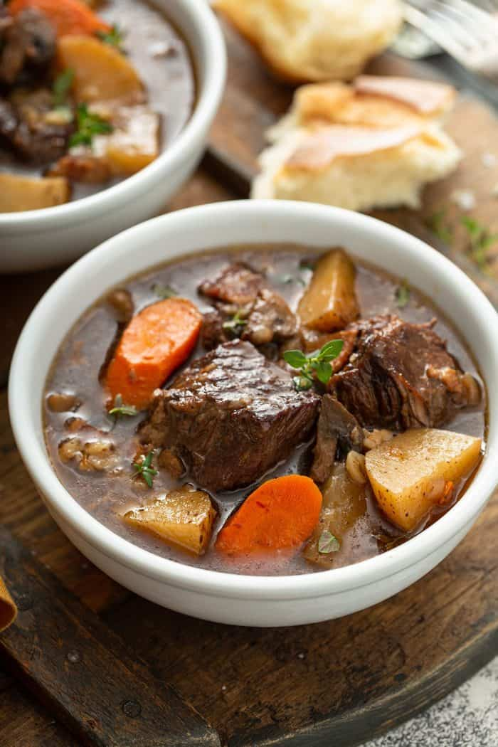 Close up of a beef and barley stew in a white bowl with crusty bread in the background