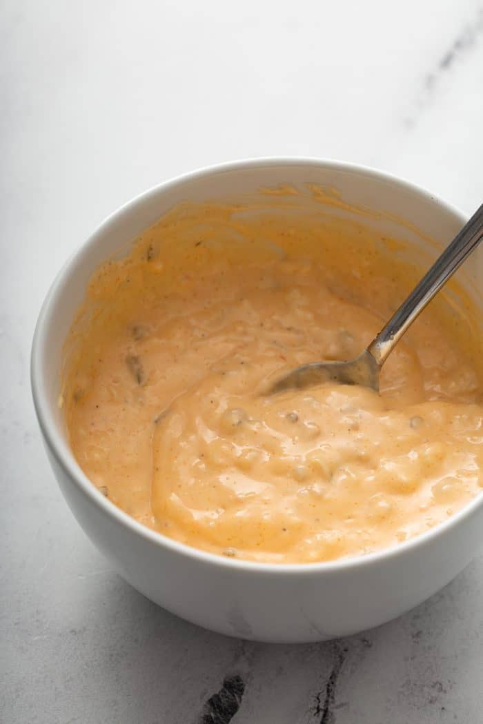 Burger sauce being stirred by a spoon in a white bowl