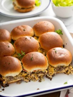 Side view of baked cheeseburger sliders in a baking dish to show the sides of the sliders