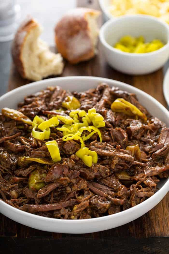Mississippi pot roast topped with sliced pepperoncini peppers in a white serving bowl