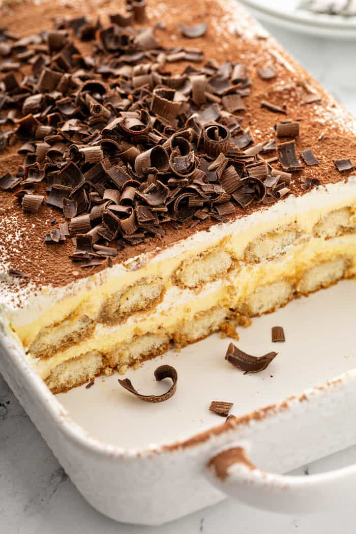 Cut tiramisu in a white baking dish