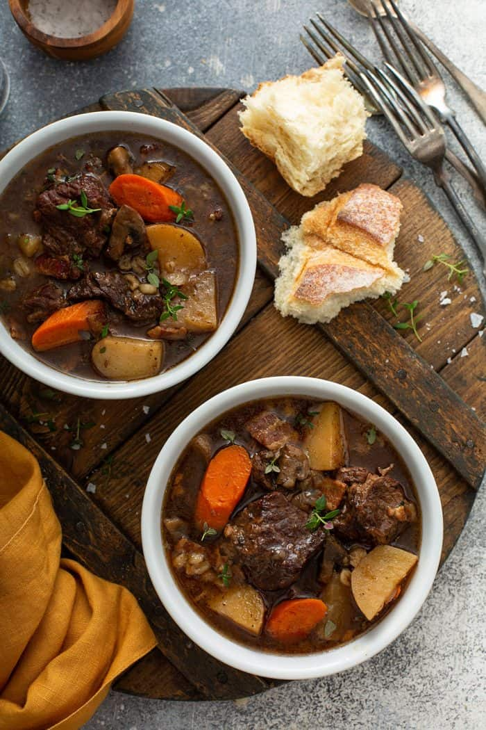Overhead shot of two white bowls filled with beef and barley stew on a wooden cutting board