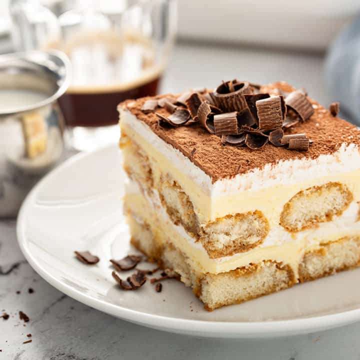 Cut slice of tiramisu on a white plate