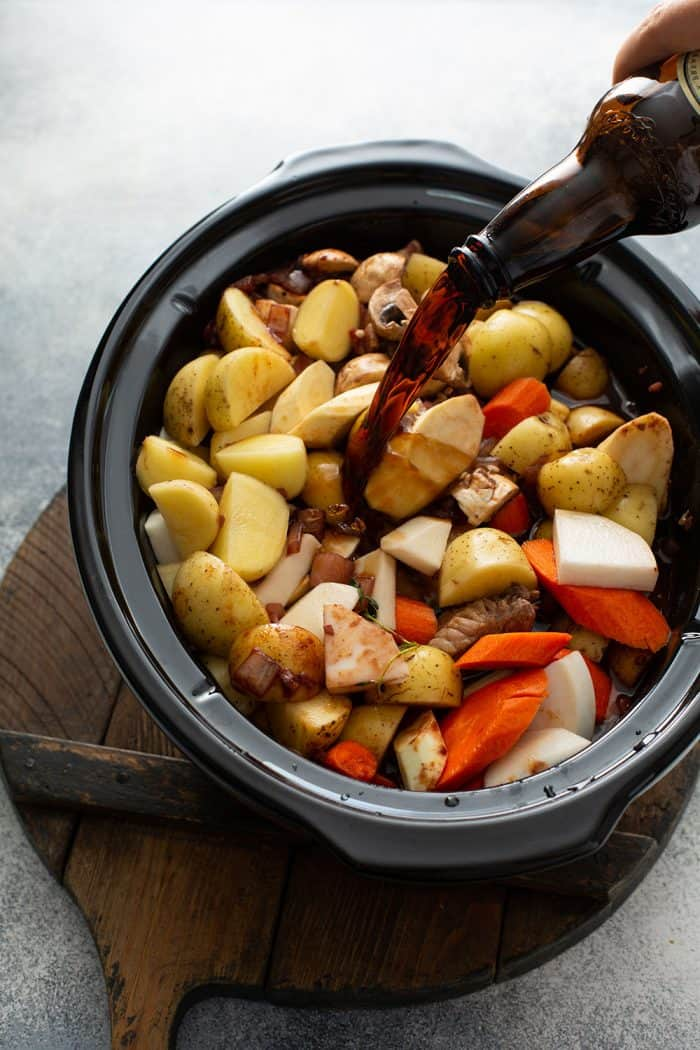 Guinness beer being poured over cut root vegetables in a slow cooker for beef and barley stew