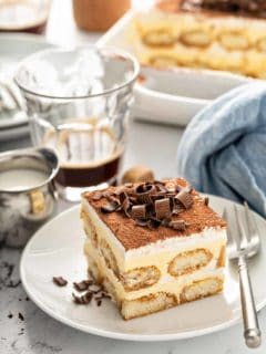 Slice of tiramisu on a white plate with coffee and a baking dish in the background