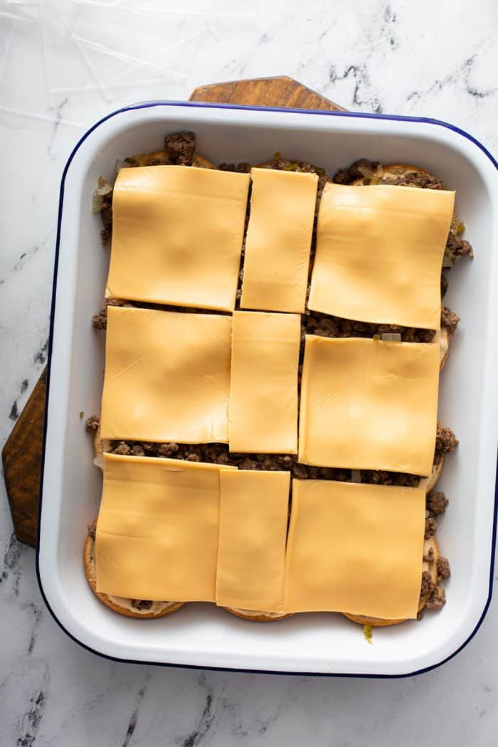 Slices of american cheese on top of slider meat in a baking dish