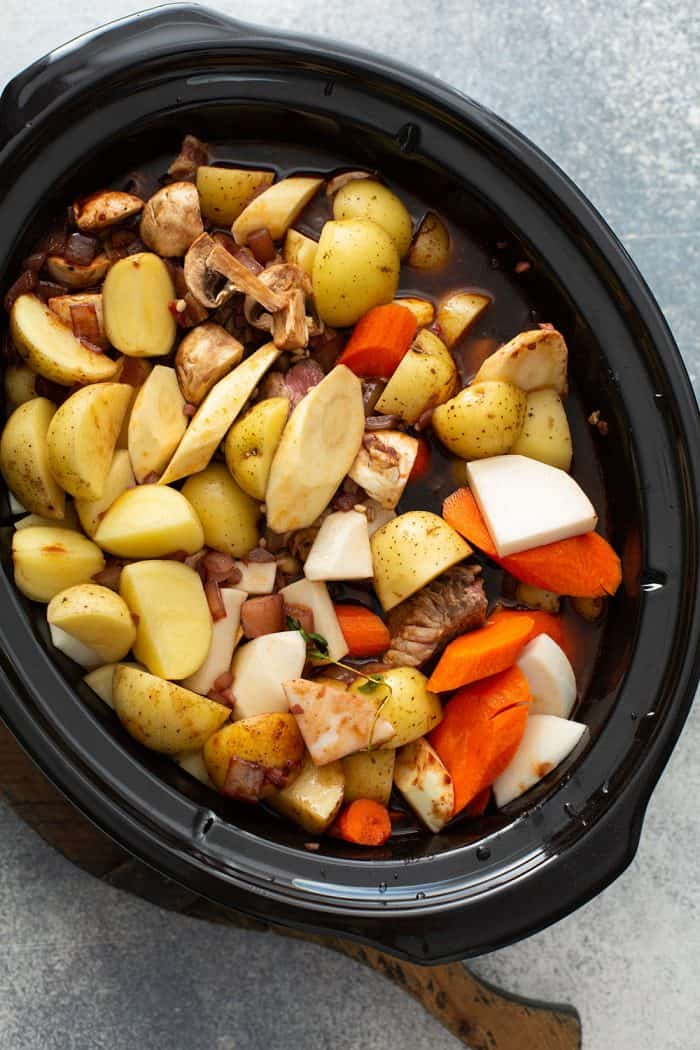 Ingredients for beef and barley stew in a slow cooker, ready to be cooked