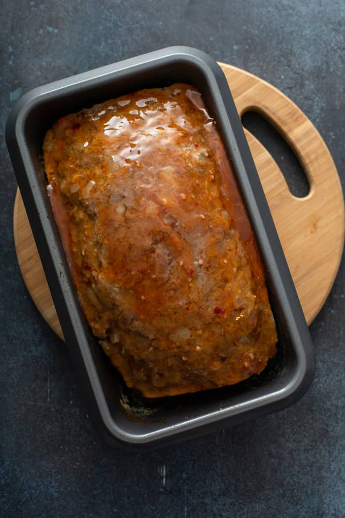 Cooked meatloaf topped with chili sauce in a loaf pan