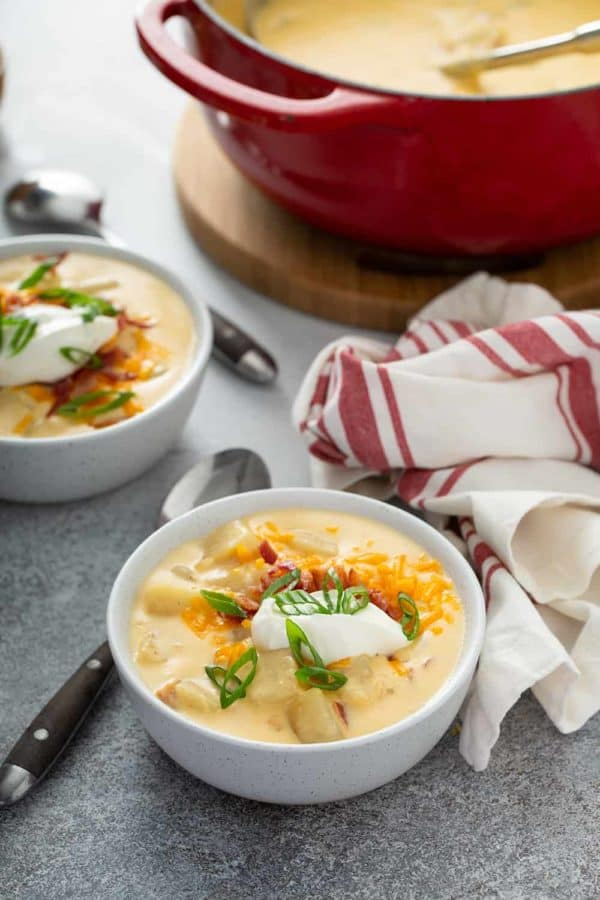 Two bowls of loaded baked potato soup on a counter in front of a dutch oven filled with soup