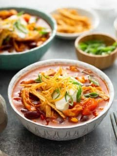 Chicken chili topped with cheese and green onions in a white bowl