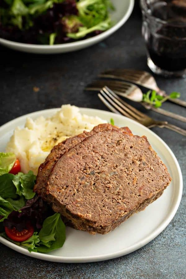 Close up of sliced meatloaf on a plate with potatoes and salad