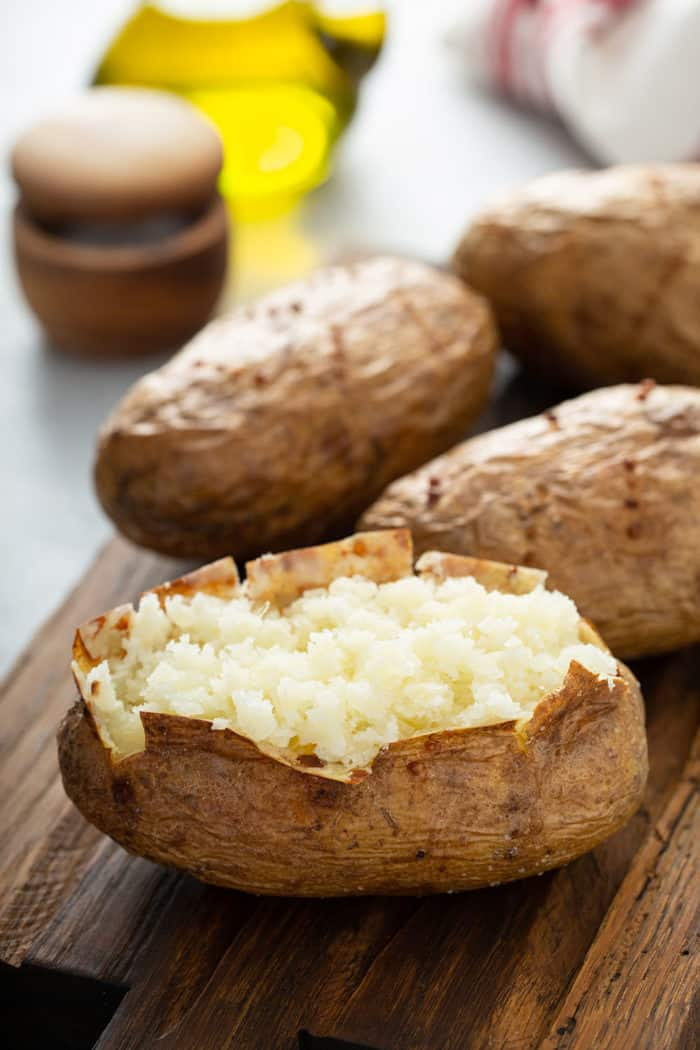 Cut open baked potato on a wooden cutting board with 3 more baked potatoes in the background
