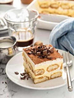 Tiramisu on a white plate, topped with chocolate curls