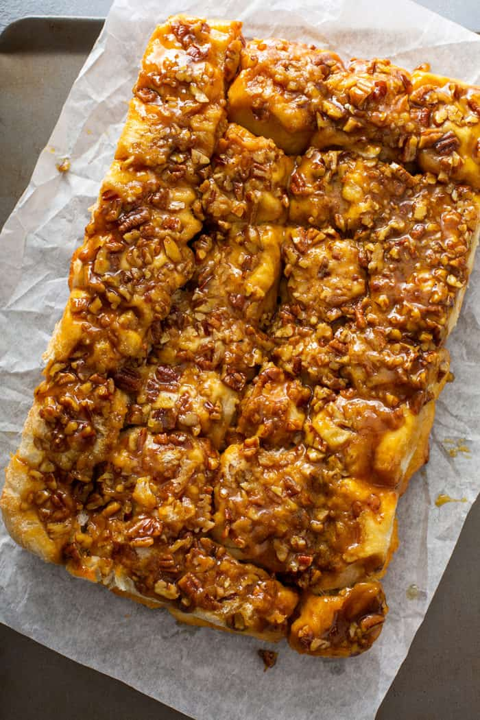 Pecan sticky buns inverted onto a piece of parchment paper