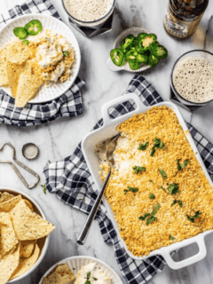 Baking dish of jalapeno popper dip on a counter surrounded by chips and beer