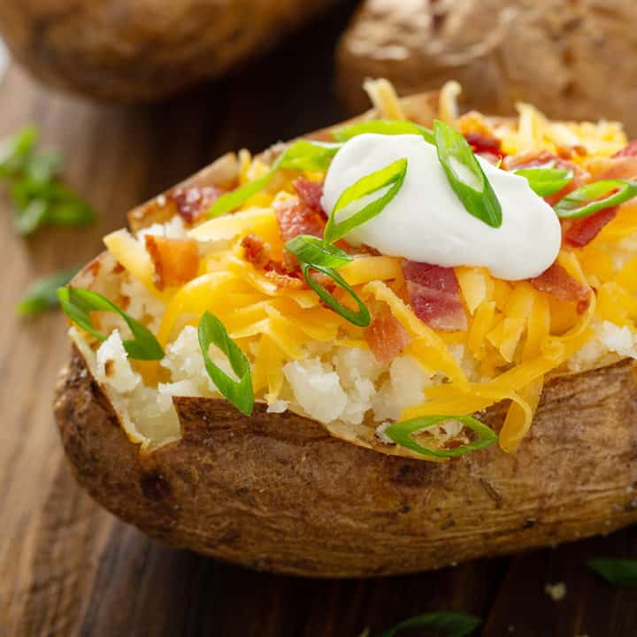 Loaded baked potato on a wooden cutting board