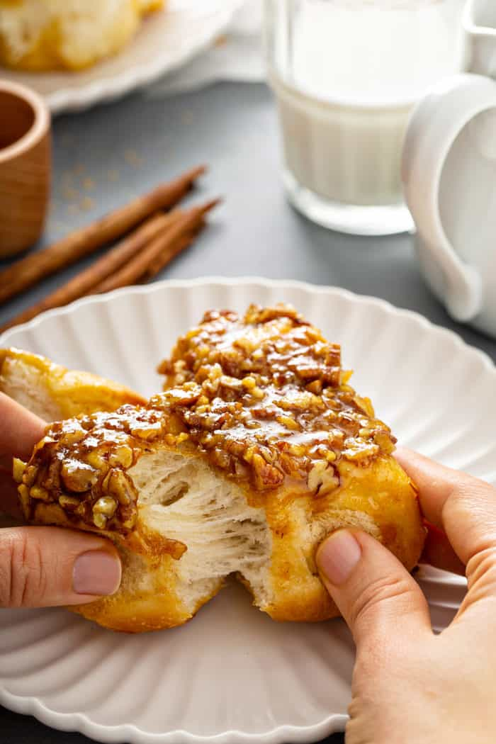 Hand pulling apart pecan sticky buns on a white plate