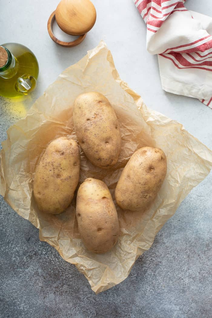 Four russet potatoes on a piece of parchment paper, ready to be prepped for baking