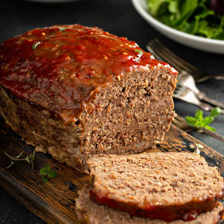 Sliced easy meatloaf with bowls of salad and mashed potatoes in the background