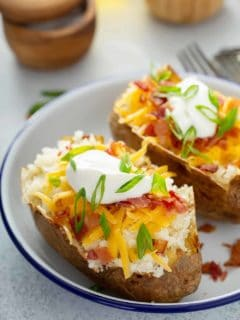 Two loaded baked potatoes on a white plate