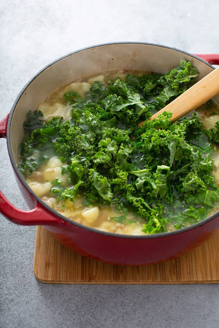 Kale being stirred into a pot of low carb zuppa toscana