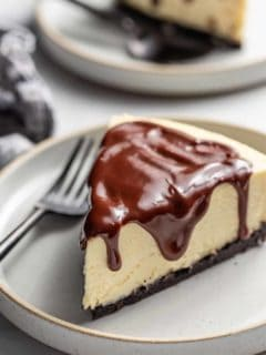 Slice of Baileys cheesecake topped with chocolate ganache on a plate