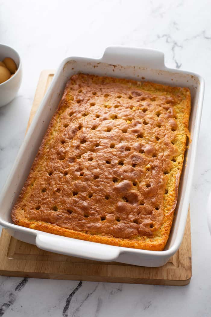 Banana cake with holes poked in it to make it into poke cake