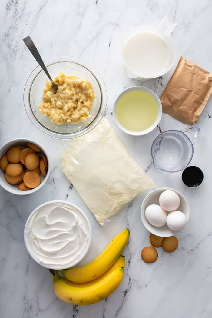 Ingredients for banana pudding poke cake arranged on a marble countertop