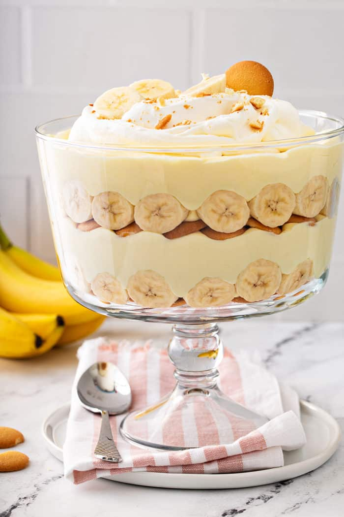 Layered banana pudding in a trifle dish, topped with whipped cream and sliced bananas