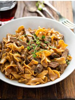 One-Pot Beef Stroganoff in a white bowl, garnished with fresh thyme