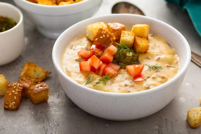 White bowl filled with cheeseburger soup topped with relish, tomatoes and croutons
