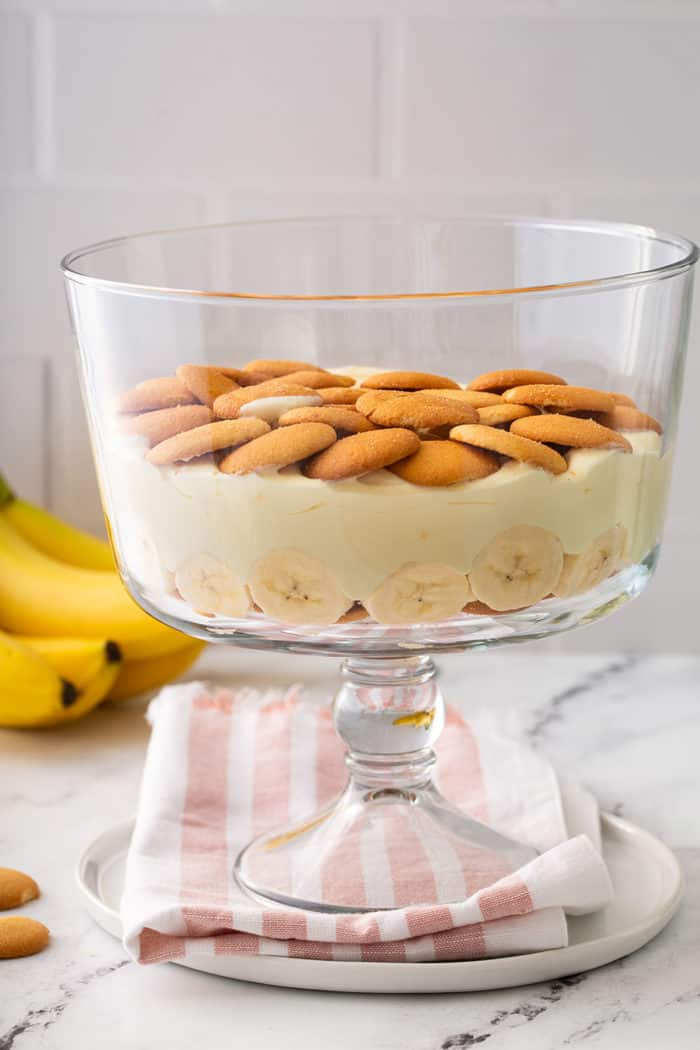 Layer of banana pudding in a trifle dish topped with a layer of nilla wafer cookies