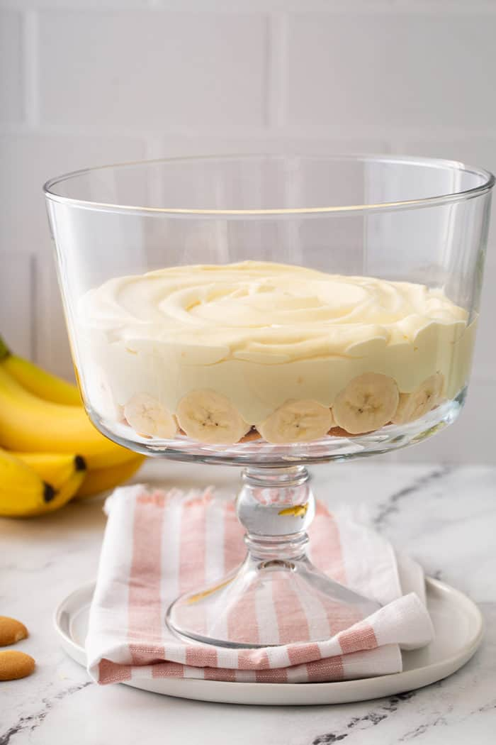 One layer of banana pudding in a trifle dish with bananas in the background
